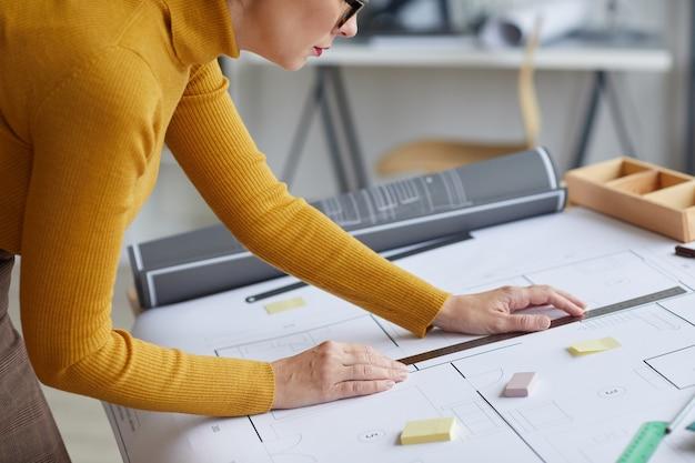 Ritratto di vista laterale ritagliata dell'architetto femminile irriconoscibile cianografie di disegno mentre si appoggia sulla scrivania al posto di lavoro,