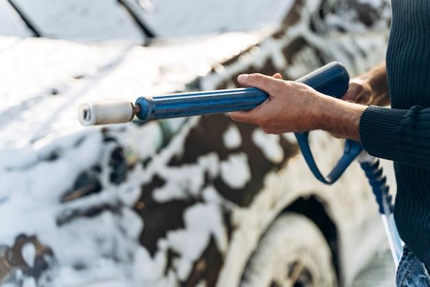 Vista ritagliata del giovane caucasico che tiene in mano una pistola ad alta pressione mentre si prepara a spruzzare sulla sua auto durante la pulizia. foto d'archivio