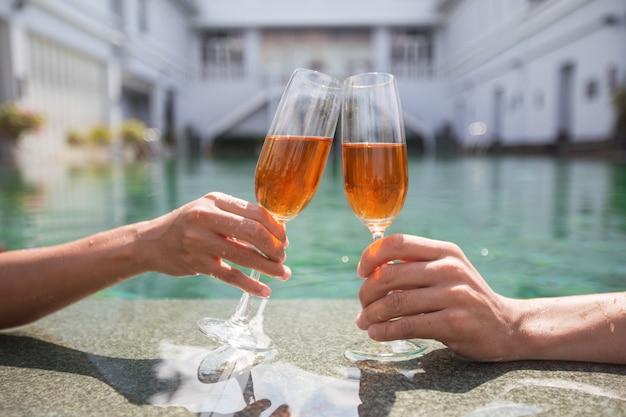 Vista ritagliata dei bicchieri di clinking delle coppie in piscina