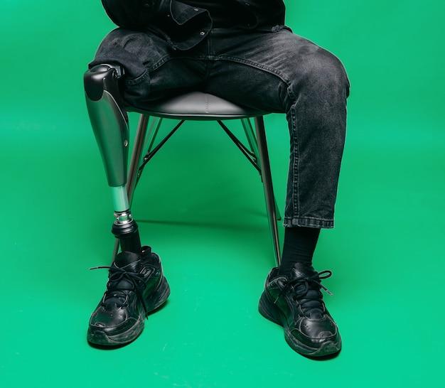Vista potata del giovane disabile con la gamba protesica, concetto artificiale dell'arto.