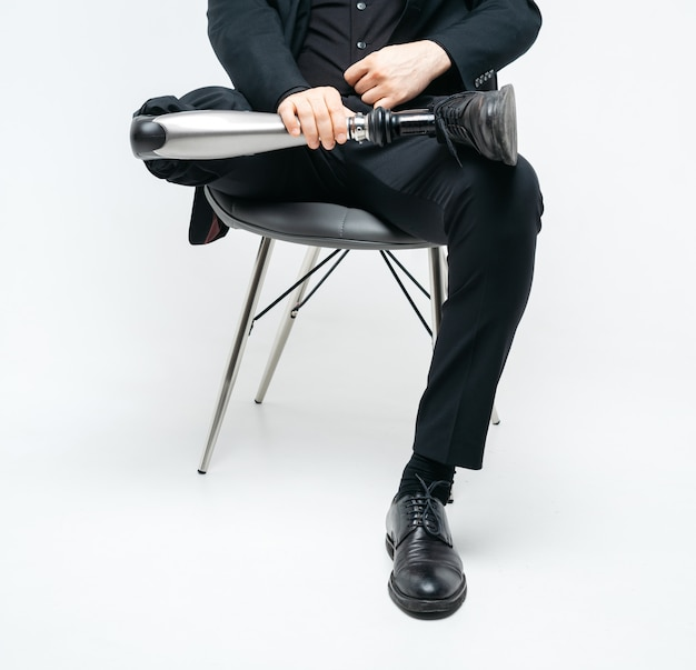 Vista potata del giovane disabile con la gamba prostetica che si siede su una sedia, concetto artificiale dell'arto