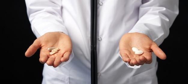 Vista ritagliata della dottoressa tenendo in mano pillole da scegliere. scelta difficile tra farmaci. concetto di farmaci placebo. concetto di assistenza sanitaria.