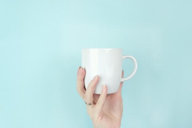 Vista ritagliata della mano femminile con tazza di caffè bianco su sfondo blu.