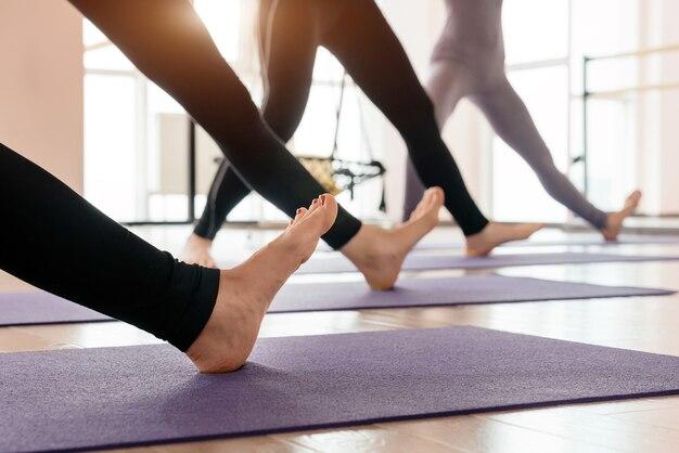 Vista ritagliata di ragazze che esercitano yoga facendo piedi e gambe che allungano in piedi in fila