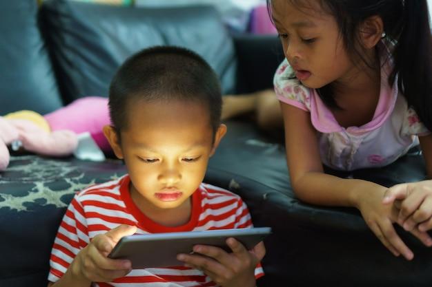 Punto di vista potato del ragazzino e della ragazza che per mezzo di una compressa digitale a casa