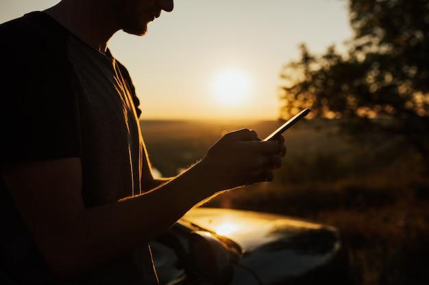 Vista potata di hipster maschio che tiene smartphone sulla natura al tramonto.