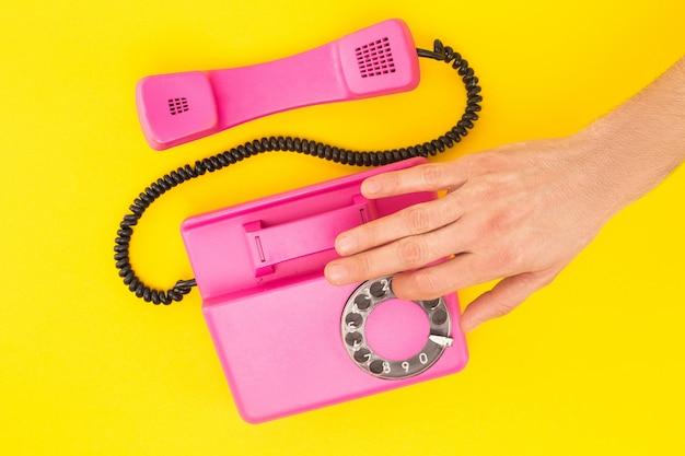 Vista ritagliata del numero di composizione uomo sul telefono isolato su giallo