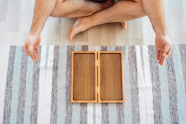 Vista ritagliata dell'uomo che esercita yoga, meditazione e seduto sul pavimento vicino al bordo del sadhu