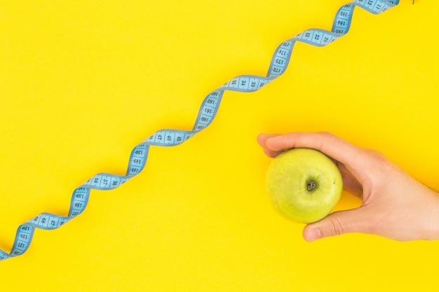 Vista potata dell'uomo che tiene mela vicino al nastro di misurazione curvo isolato su giallo