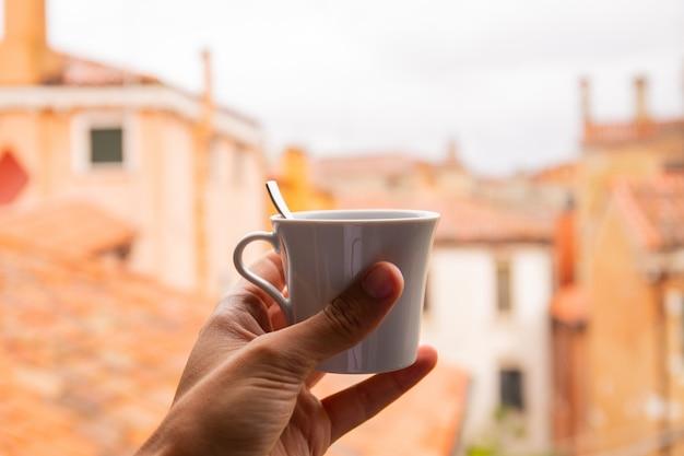 Vista potata del caffè della tenuta dell'uomo con paesaggio urbano su fondo a venezia, italia.