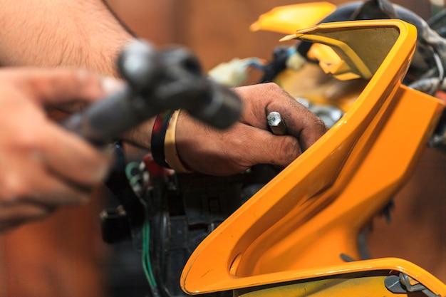 Vista ritagliata del meccanico motociclistico, tecnico
