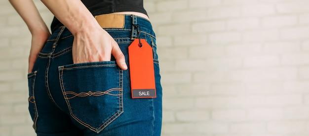 Donna sottile vista potata in jeans con etichetta venerdì nero, copia spazio.