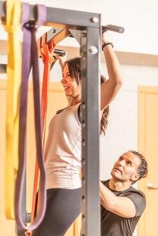 Vista ritagliata di una sportiva che fa esercizio di pull up con barra con l'aiuto di un allenatore in palestra. concetto di esercizio con attrezzature in palestra.