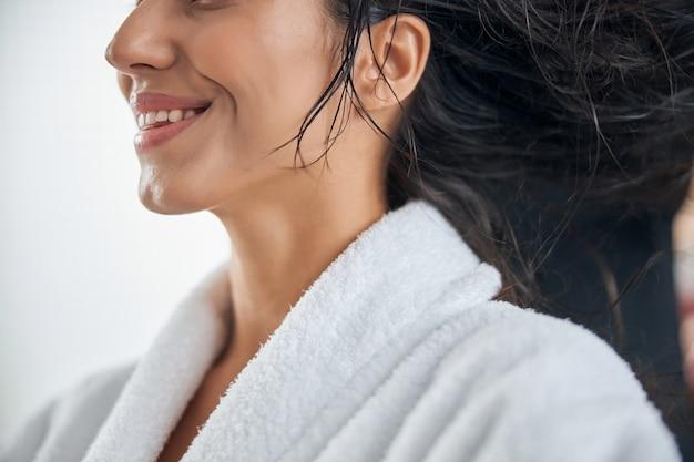 Vista ritagliata della donna con i capelli bagnati e un ampio sorriso