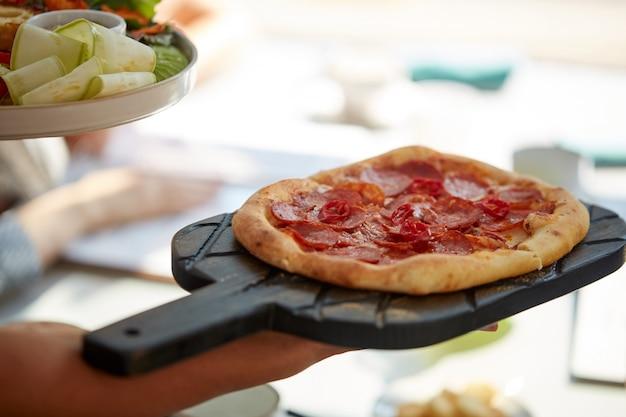 Il cameriere ritagliato porta una gustosa pizza italiana ai clienti nel ristorante