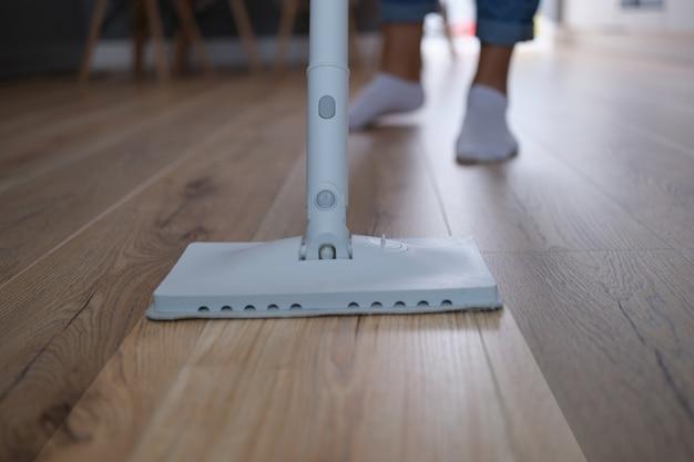 Donna tagliata che pulisce il pavimento in laminato di legno usando un mocio umido