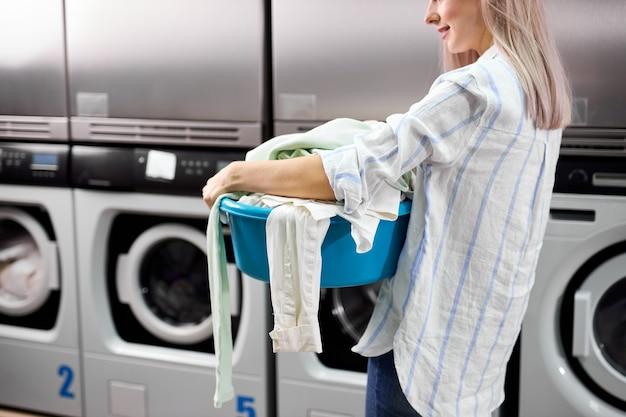 Ritagliata donna in piedi da sola con vestiti sporchi nella lavanderia self-service con asciugatrici. femmina in abbigliamento casual sta tenendo il bacino con i vestiti. concentrarsi sulla donna