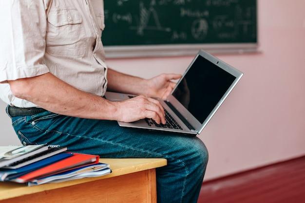 Immagine potata dell'insegnante che tiene un computer portatile aperto e che si siede sulla tavola.