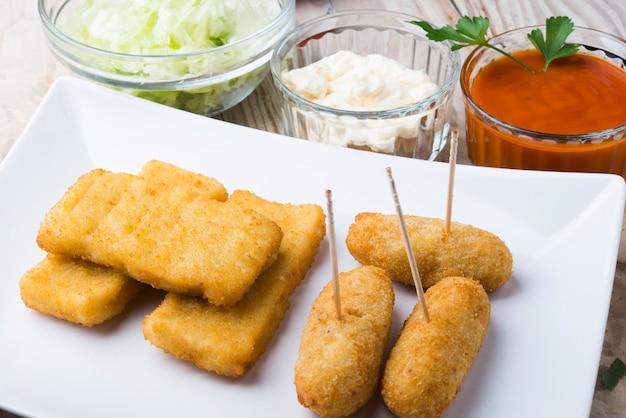 Palline di crocchette e diversi tipi di salse su un piatto