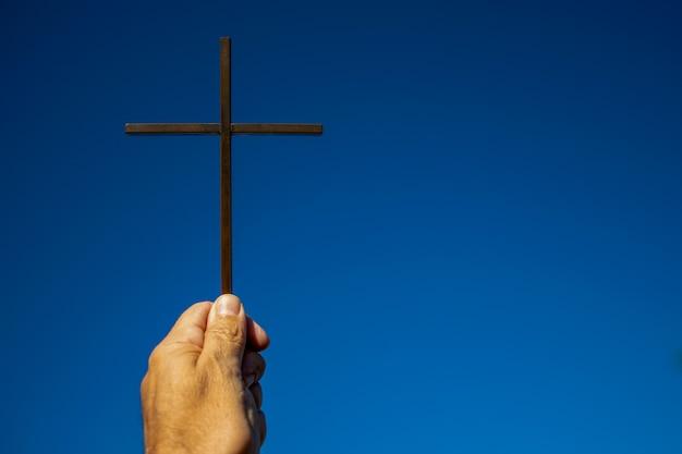Croce sul cielo blu sorretta dalla mano dell'uomo