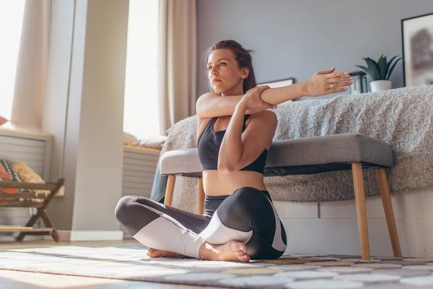 Stretching a spalla incrociata. la donna a casa fa un riscaldamento e un allungamento.