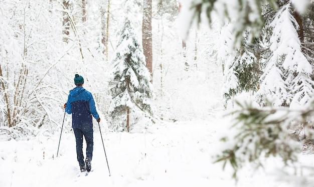 Sciatore di fondo in cappello con pompon con bastoncini da sci nella foresta invernale innevata.