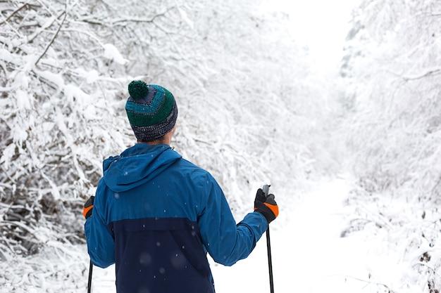 Sci di fondo nella foresta invernale, sciatore in cappello con pompon con bastoncini da sci