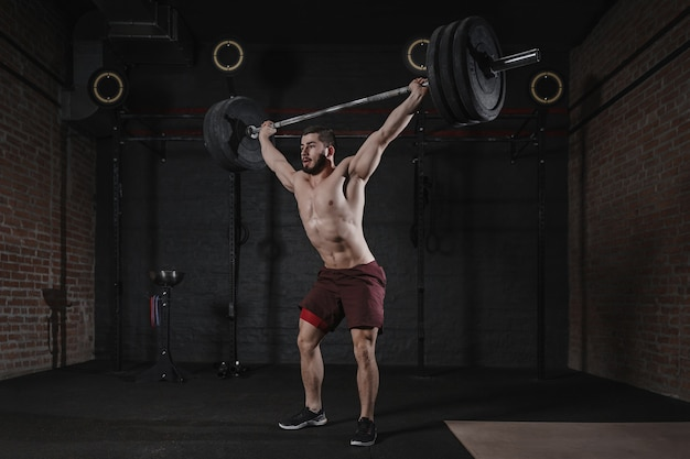 Cross fit atleta sollevamento bilanciere in testa in palestra