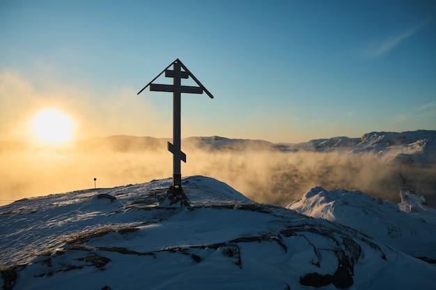 Croce sull'alba fredda della penisola di kola a teriberka