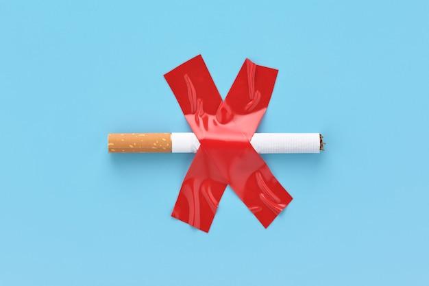 Sigaretta barrata, incollata con nastro adesivo rosso, concetto non fumatori.