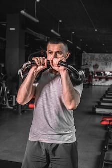 Allenamento crossfit. uomo di forma fisica che fa un allenamento con i pesi sollevando kettlebell.