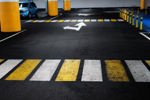 Attraversamento pedonale in un parcheggio sotterraneo con uno sfondo sfocato.