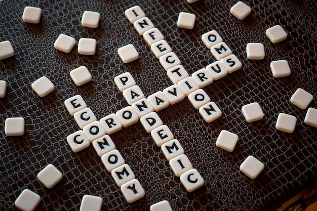 Pezzi di gioco di parole crociate che formano parole legate al coronavirus