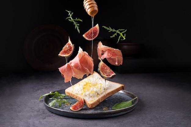 Crostini con prosciutto, ricotta e fichi, prosciutto italiano volante e frutta su sfondo scuro, pane tostato con jamon, primo piano.