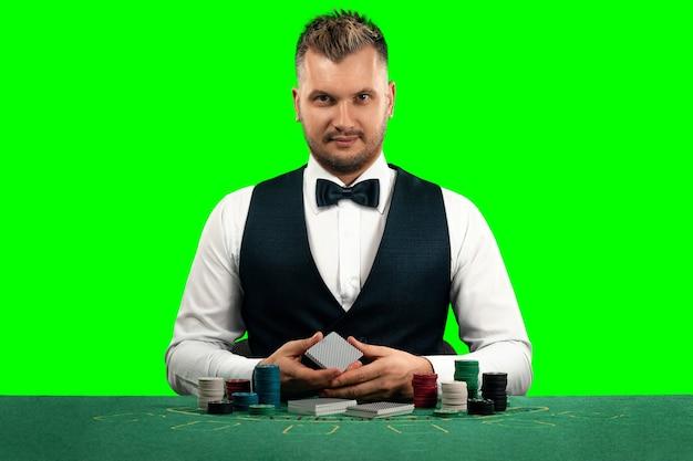 Un uomo croupier si siede a un tavolo con fiches e carte da gioco isolare lo schermo verde