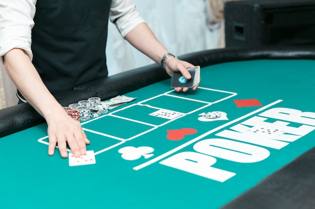 Croupier al tavolo da poker del casinò. fiches e carte in tavola.