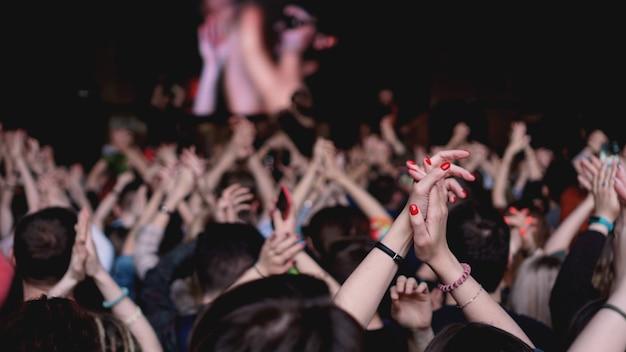 Folla al concerto - folla esultante in luci di scena colorate e luminose. pubblico al festival di musica all'aperto