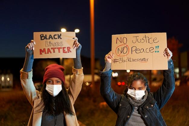 Folla di manifestanti di etnia mista con striscioni che protestano contro la brutalità e il canto della polizia. ritagliare vista di giovani con cartellone in cartone e bandiera americana che camminano e gridano. la vita nera è importante