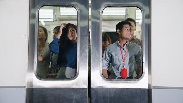 Folla di persone su un viaggio in treno della metropolitana pubblico affollato occupato. pendolarismo e concetto di stile di vita urbano.