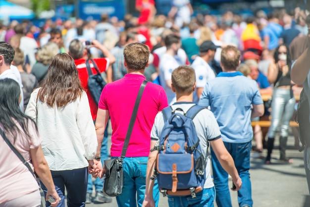 Folla di persone che camminano sulla strada della città