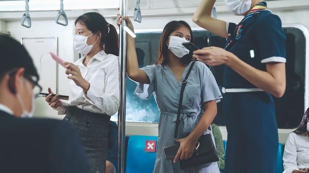 Folla di persone che indossano la maschera facciale su un affollato viaggio in metropolitana pubblica