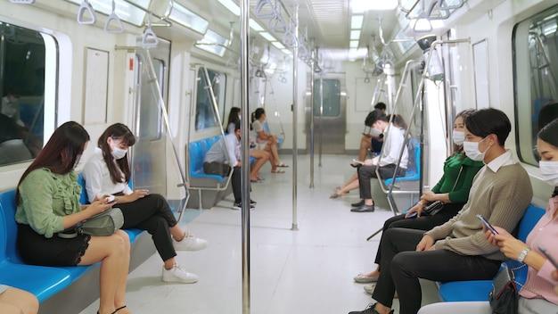 Folla di persone che indossano la maschera per il viso su un affollato viaggio in treno della metropolitana