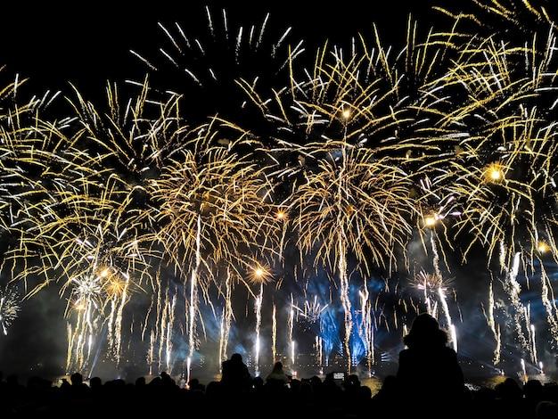 Folla a guardare varietà di fuochi d'artificio colorati. saluta con lampi gialli e oro, sullo sfondo del cielo notturno.