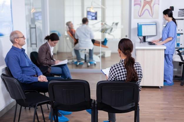 Area di attesa affollata di stomatologia con persone che compilano il modulo per la consultazione dentale. stomatoloy specialista in odontoiatria per il trattamento della cavità della donna anziana. receptionist che lavora al computer.