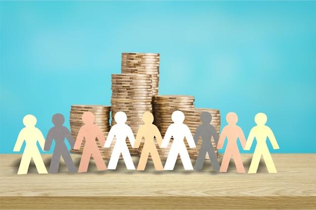 Concetto di crowdfunding. carta ritagliata figure umane intorno alla pila di banconote da cento dollari