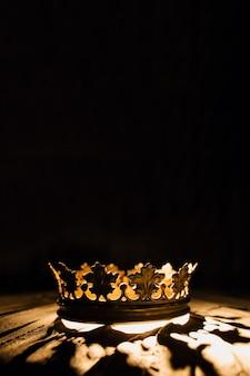 Una corona su sfondo nero è evidenziata da un raggio dorato battaglia per il trono