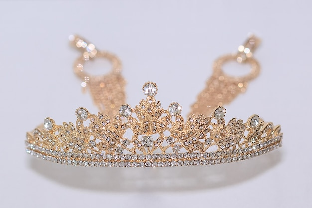 Una corona e orecchini su uno sfondo bianco. il concetto di una festa di matrimonio, damigella d'onore e addio al nubilato.