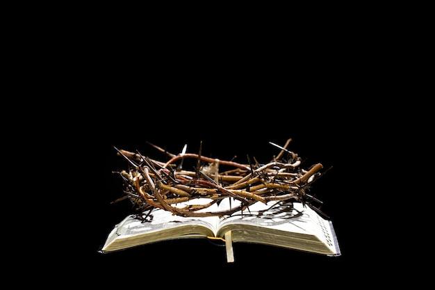 La corona di spine giace sul libro della bibbia nell'oscurità. il concetto di settimana santa e la crocifissione di gesù.