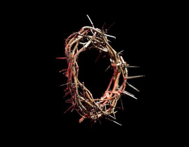 Corona di spine con una sfumatura rossa di luce nell'oscurità. il concetto di settimana santa, sofferenza e crocifissione di gesù.