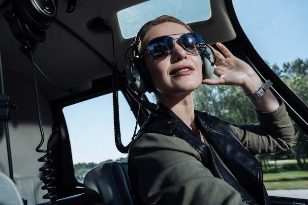 Istruzioni cruciali. bello giovane pilota femminile seduto in una cabina di elicottero e ascoltando le istruzioni dei controllori del traffico aereo